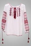Kvinnlig nationell folklore för skjorta, en folk dräkt Ukraina, på bakgrund för grå vit Arkivbild