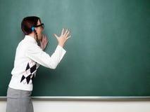 Kvinnlig nerd som skriker in i svart tavla Arkivbilder