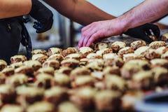 Kvinnlig och manlig kock Putting Ingredients av hamburgare på en skivad brödspridning på en tabell i svarta handskar - begrepp av royaltyfria foton
