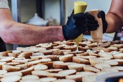 Kvinnlig och manlig kock Putting Ingredients av hamburgare på en skivad brödspridning på en tabell i svarta handskar - begrepp av arkivbild