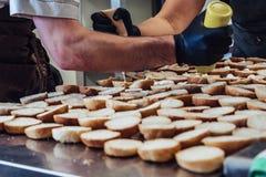 Kvinnlig och manlig kock Putting Ingredients av hamburgare på en skivad brödspridning på en tabell i svarta handskar - begrepp av royaltyfria bilder