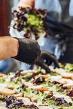 Kvinnlig och manlig kock Putting Ingredients av hamburgare på en skivad brödspridning på en tabell i svarta handskar - begrepp av arkivfoto