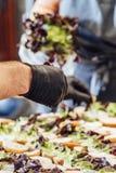 Kvinnlig och manlig kock Putting Ingredients av hamburgare på en skivad brödspridning på en tabell i svarta handskar - begrepp av royaltyfri bild