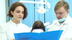 Kvinnlig och manliga tandläkare som rymmer en mapp av dokument som framme diskuterar behandling av patienten i tand- stol stock video