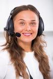 Kvinnlig operatör som talar med kunden som använder hörlurar med mikrofon arkivbild