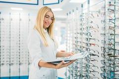 Kvinnlig optiker med exponeringsglaskatalogen i händer arkivfoto