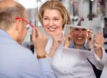 Kvinnlig optiker som konsulterar den mogna manliga kunden om ramar, genom att använda en spegel Royaltyfri Bild
