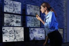Kvinnlig ordningsvakt med den bärbara sändaren som övervakar moderna CCTV-kameror fotografering för bildbyråer