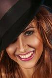 Kvinnlig på hatten och toothy leende Arkivbilder