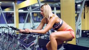 Kvinnlig på idrottshallcykeln som gör cardio övning stock video