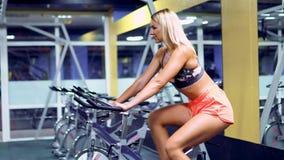 Kvinnlig på idrottshallcykeln som gör cardio övning arkivfilmer
