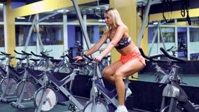 Kvinnlig på idrottshallcykeln som gör cardio övning lager videofilmer
