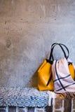 Kvinnlig påse för lyxigt gulingläder på grå väggbackgroud arkivbilder