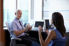 Kvinnlig patient för doktor In Consultation With i regeringsställning royaltyfri fotografi