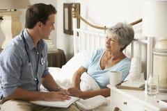 Kvinnlig patient för doktor Talking With Senior i säng hemma royaltyfria bilder
