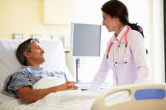 Kvinnlig patient för doktor Talking To Male i sjukhusrum Arkivfoton
