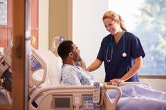 Kvinnlig patient för doktor Talking To Male i sjukhussäng Arkivbilder