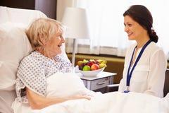 Kvinnlig patient för doktor Talking To Senior i sjukhussäng arkivbilder