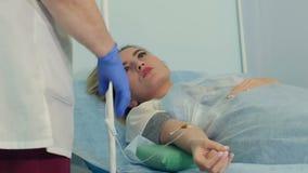 Kvinnlig patient på en droppande som talar till en sjuksköterska stock video