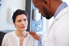 Kvinnlig patient som uppmuntras av doktor In Hospital Room arkivfoton