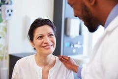 Kvinnlig patient som uppmuntras av doktor In Hospital Room royaltyfria foton