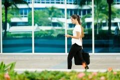 Kvinnlig pendlare för affärskvinna som går kontoret som smsar på telefonen Arkivfoton