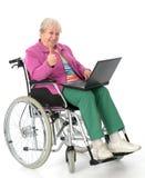 Kvinnlig pensionär i rullstol med datoren arkivfoton