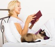 Kvinnlig pensionär med kattläseboken Royaltyfri Foto