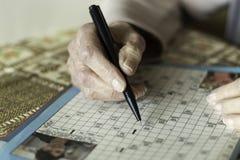 Kvinnlig pensionär som gör korsord arkivbild