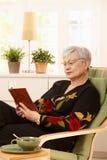 Kvinnlig pensionär som hemma läser Arkivfoton