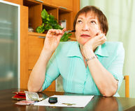 Kvinnlig pensionär som inomhus gör finansiellt arbete Fotografering för Bildbyråer