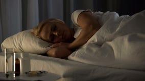 Kvinnlig pensionär som sover i säng, piller och exponeringsglas av vatten nära tabellen, sjukdom arkivfoton