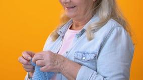 Kvinnlig pensionär som sticker den blåa halsduken och in camera ler, handgjort hantverk lager videofilmer