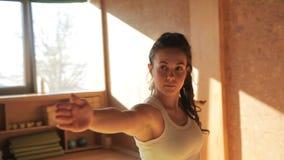 Kvinnlig personlig instruktör som gör asanas som blir på matting i yogastudio arkivfilmer