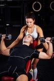 Kvinnlig personlig konditioninstruktör som hjälper en ung man på idrottshallen Royaltyfria Foton