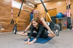 Kvinnlig personlig ung flicka för konditioninstruktörportion som gör övningar i idrottshall på konditionöglasremmar Sport idrotts arkivfoto
