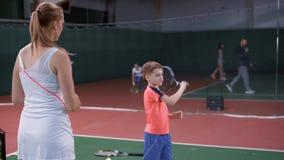 Kvinnlig pojke för tennisinstruktörundervisning hur man slår bollen med en racket lager videofilmer