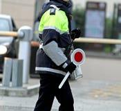 Kvinnlig polis med skoveln, medan rikta trafik Arkivfoton