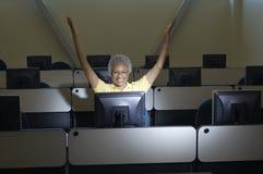 Kvinnlig professor Celebrating Victory In Computer Classroom Royaltyfri Bild