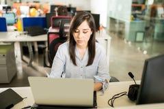 Kvinnlig programvarubärare som arbetar på hennes skrivbord royaltyfri bild