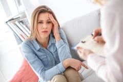 Kvinnlig psychologystterapiperiod med klienten som sitter inomhus den fundersamma flickan arkivfoto
