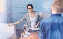 Kvinnlig psykolog som pekar på soffan, medan tala till barnpatienten royaltyfri foto