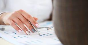 Kvinnlig punkt f?r penna f?r silver f?r arminnehav i finansiell graf arkivbilder