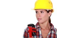Kvinnlig rörmokare med en skiftnyckel. Arkivfoto