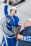 Kvinnlig rörmokare som arbetar med ventilationsrör royaltyfria foton