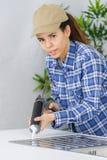 Kvinnlig rörmokare som sätter silikontätningsmedel runt om diskho arkivfoto