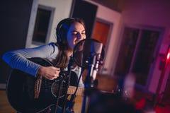 Kvinnlig röst- konstnär som sjunger i en inspelningstudio Royaltyfri Bild
