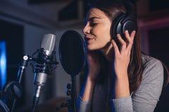 Kvinnlig röst- konstnär som sjunger i en inspelningstudio Arkivbilder