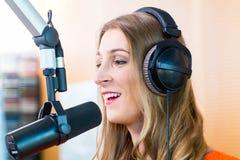 Kvinnlig radiopresentatör i radiostation på luft Royaltyfri Foto