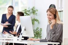 Kvinnlig receptionist med hörlurar med mikrofon på skrivbordet royaltyfria foton